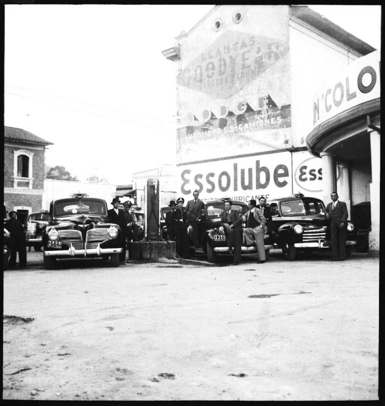 Choferes y automóviles esperando gasolina en las bombas de la ciudad