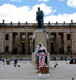 """Wikimedia Commons. Las obras de remodelación de la plaza comenzaron el 25 de enero de 1960, el 10 de febrero fue desmontada la estatua del pedestal y los trabajos finalizaron el sábado 16 de julio del mismo año con la inauguración de la nueva Plaza de Bolívar, que estuvo a cargo del presidente Alberto Lleras Camargo. Esta obra hizo parte del programa de celebración del sesquicentenario de la independencia nacional. El monumento al Libertador contó desde entonces con un """"nuevo pedestal hexagonal en piedra que se apoyó sobre una plataforma en concreto"""" en cuya cara frontal tenía grabado el nombre de """"Bolívar"""" mientras que en las cuatro caras laterales se ubicaban los relieves originales. Los trabajos fueron concluidos el 2 de julio de ese mismo año. La estatua del Libertador se situó mirando hacia el costado norte de la Plaza, donde se encuentra el Palacio de Justicia."""